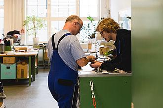 Werkstattmitarbeiter im Beratungsgespräch mit einem Studenten
